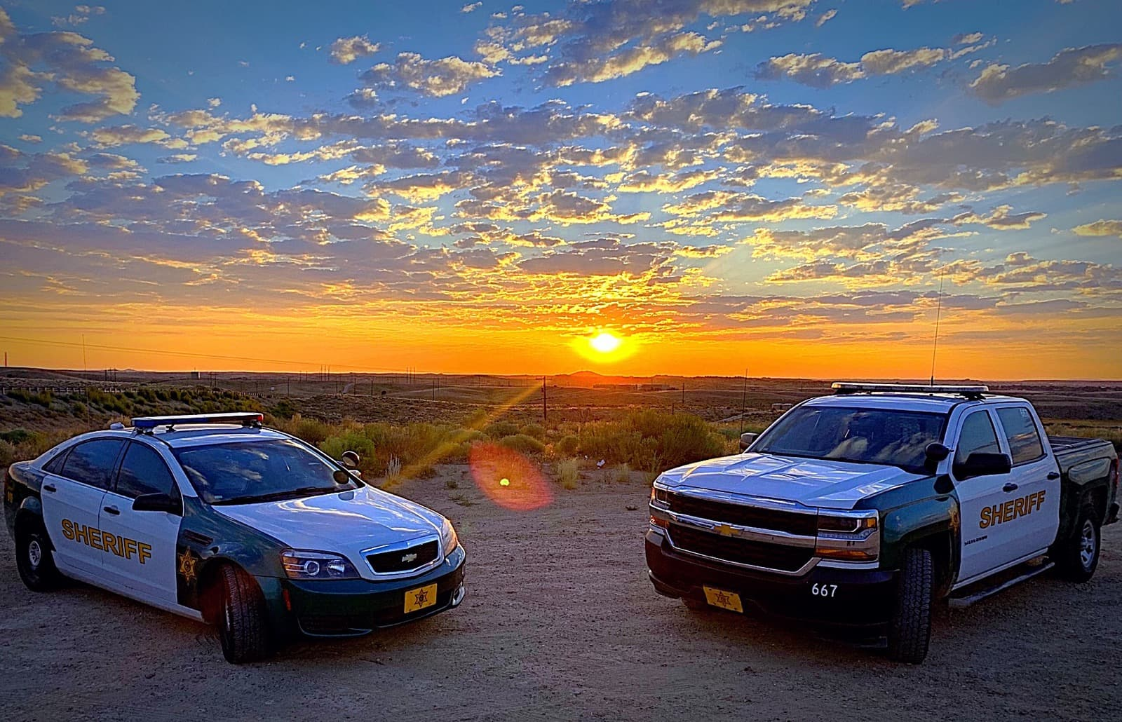 4 door sedan sheriffs office vehicle and 4 door sheriffs truck parked next to each other in front of a sunrise